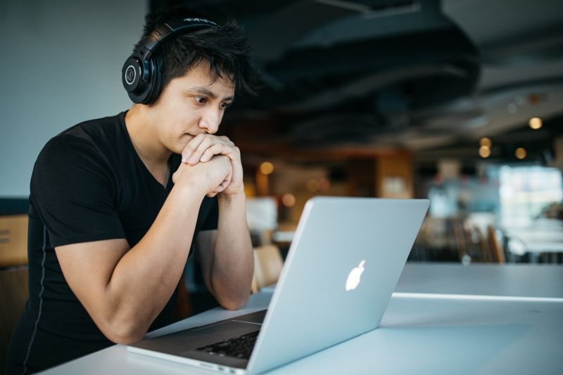 Jonge man geconcentreerd achter zijn notebook