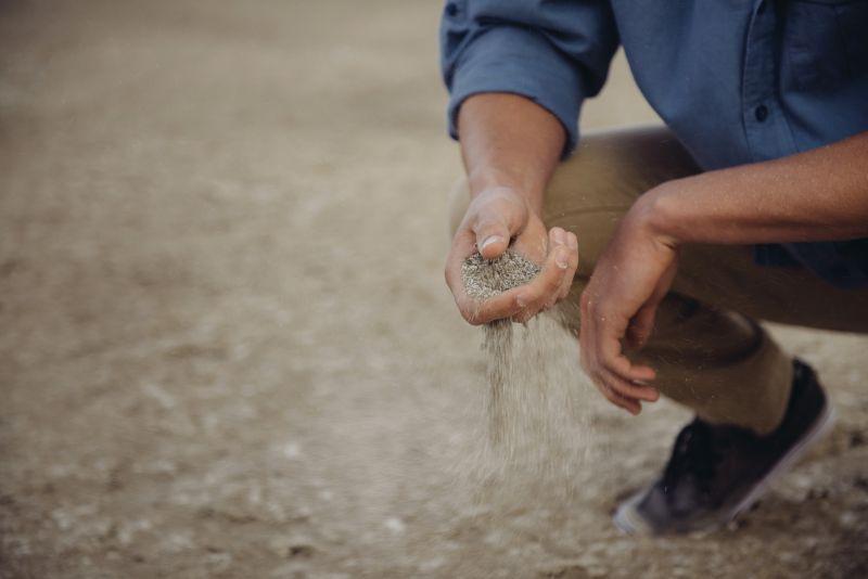 Man laat zand uit z'n hand glijden